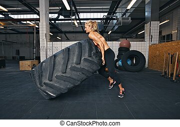 Fit female athlete flipping a huge tire Muscular young woman...