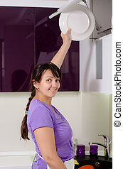 Attractive housewife doing the dishes standing at the...