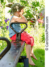 Little boy sulking as he sits on a seesaw in a lush green...