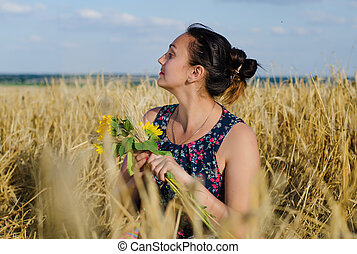 Laughing woman holding flowers in a wheat field - Laughing...