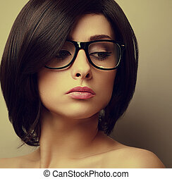 Beautiful woman with black hair in fashion glasses. Closeup...