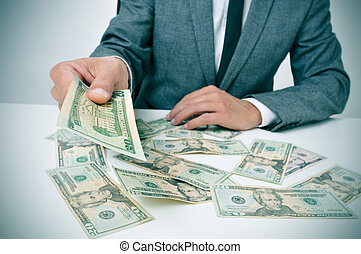 man in suit giving dollar bills - man in suit sitting in a...