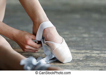 Taking off the ballet shoes after rehearsal or performance -...