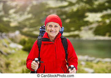 Senior woman hiking - Senior tourist woman hiking at the...