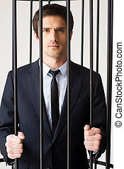 White collar crime. Depressed young man in formalwear standing behind a prison cell and looking at camera