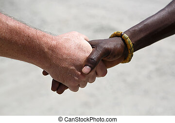 Handshake between a Caucasian and an African on gray...