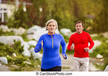 Senior couple running - Senior couple jogging round the tarn...