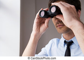 Looking for new opportunities. Confident young man in shirt and tie looking through binoculars