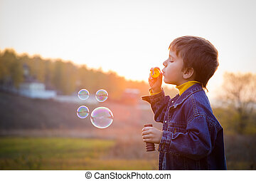 Boy with soap bubbles - Smiling boy blowing up the soap...