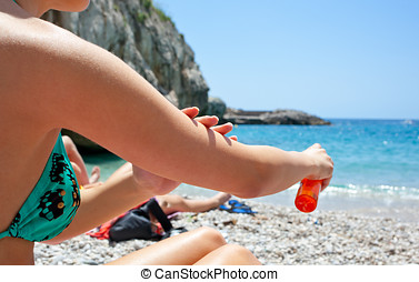 Woman applying suntan lotion oil to her body at the beach
