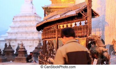 Tourists walk and spin prayer - KATHMANDU, NEPAL - APRIL 5,...
