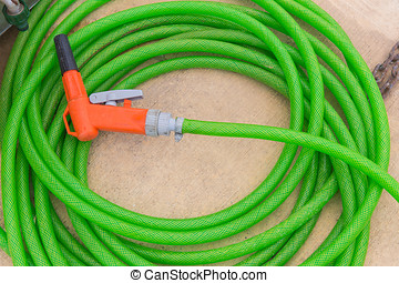 garden hose - green with orange spray hose at the end of