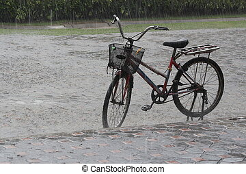 old bicycle on the street in the pouring rain