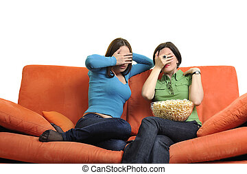female friends eating popcorn and watching tv at home