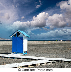 Wooden colorful cabin on a desert beach
