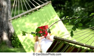Woman is reading book in hammock