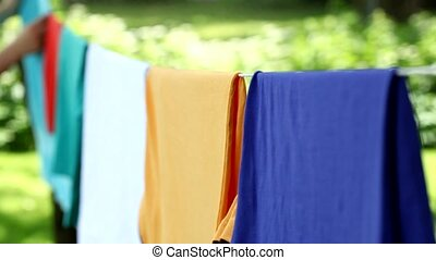 Woman taking dry clothes from cord