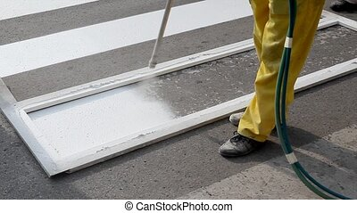 Roadworks, painting lines - Worker spraying of pedestrian...