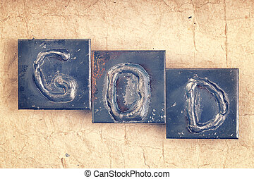 """The word """"GOD"""" made from metal letters on an old vintage paper b"""