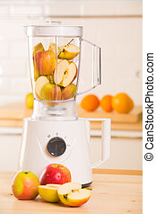 White blender with apples on a wooden table.