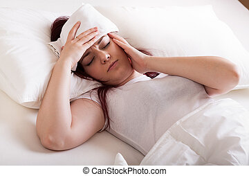 Young woman with migraine lying in bed and doing wraps