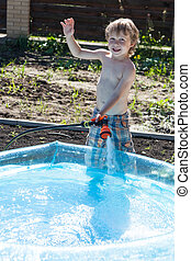 Boy fills up with water - Boy fills inflatable pool with a...
