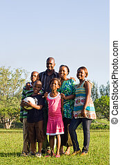 african american family in park - parents and kids posing in...