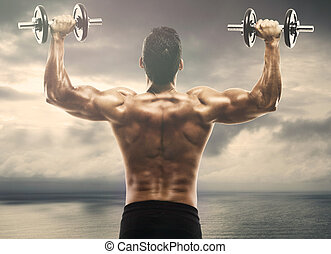 Muscle man lifting weights on outdoor