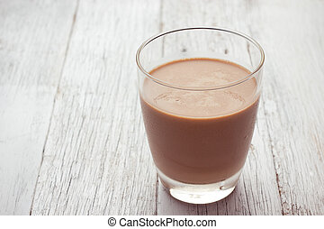 Glass with chocolate - A glass of chocolate milk on wooden...