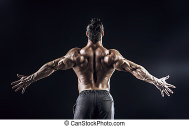 champion - Beautiful muscular man bodybuilder posing back...