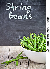 green string beans in a bowl and blackboard