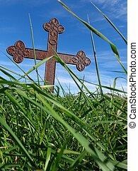 Christian cross in green field