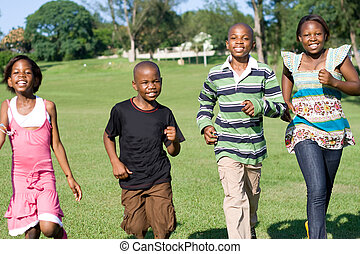 kids running in park - four friends running together in park