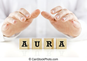 Word - Aura - on wooden cubes with a man in a white shirt...