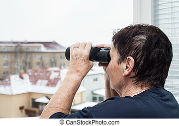 Senior woman with binoculars looking out from window.