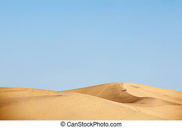 two people walking in desert dunes - two people walking in...