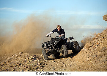 teen riding quad ATV in hills - teen male riding a quad ATV...