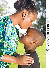 mothers touch - an african mother kissing her sons forehead