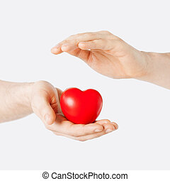 male hands with small red heart - health, medicine and...