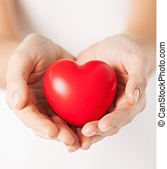 female hands with small red heart - health, medicine and...