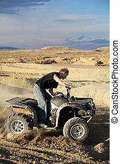 teen riding quad ATV in the hills - teen male riding a quad...