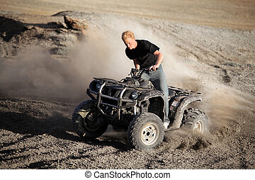 teenager riding quad - four wheeler - teenager male riding a...
