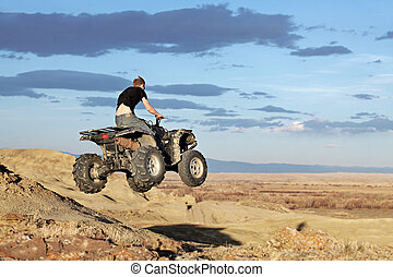 teen on quad - four wheeler - teen jumping on a quad - four...