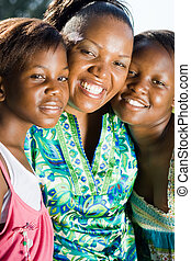happy african mom - a mom with her two daughters by her side