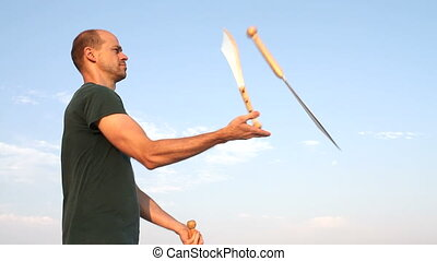 Man Juggling Knives - Man throwing three knives in the air...