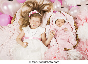 Baby birthday party gifts. Girl holding newborn sister hand.