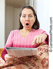amazed mature woman looks newspaper - fright and amazed...