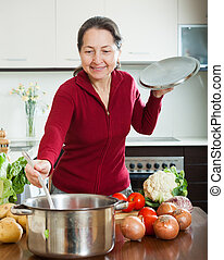mature woman cooking soup in her kitchen