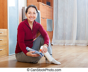 mature woman rubbing wooden floor with rag and cleanser at...