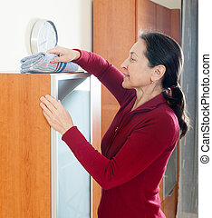 Woman cleaninig at home - mature housewife dusting glass on...